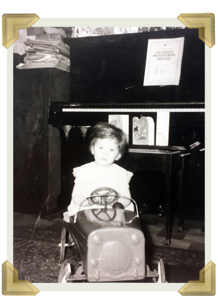 Elaine Roberts on her birthday with her new pedal car, in front of Dad's piano, which was the heart of the house with music played every day, Russell Street
