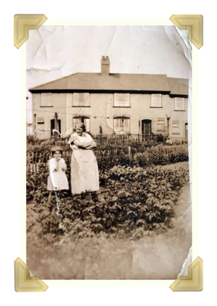 Alice Silwood in her garden growing veg for the war. Violet aged about 6, Alice was late 40s. Taken around 1938-9